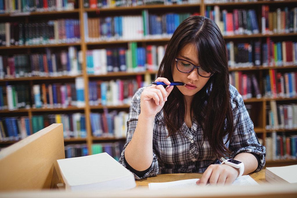 Studentin liest in der Bibliothek